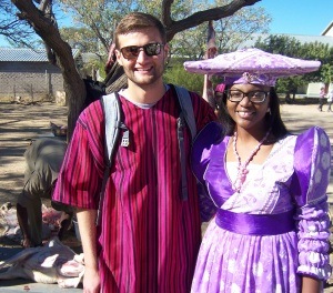 Eric with Brittany who is beautiful in traditional Herero dress.  Yes, that is Mike in the background skinning and gutting one of the three goats slaughtered in our honor.